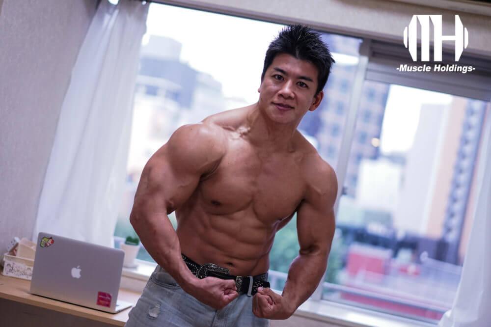 肩や上腕三頭筋や大胸筋を強調するポージングをするケビン