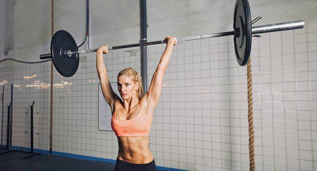 肩を鍛える筋トレの種目であるミリタリープレスを行う女性