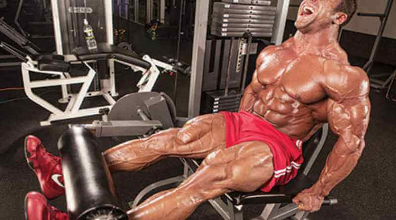 レッグエクステンションを正しいフォームで行い大腿四頭筋を鍛えるマッチョな男性