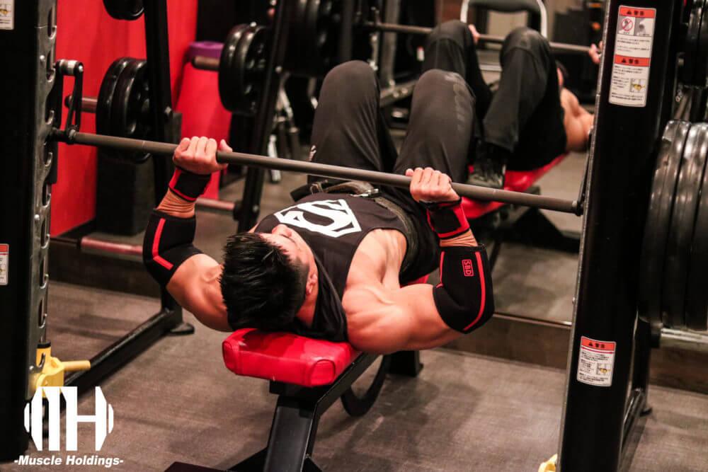 上腕三頭筋を鍛える種目であるスミスマシンクローズグリップベンチプレスを行うケビン