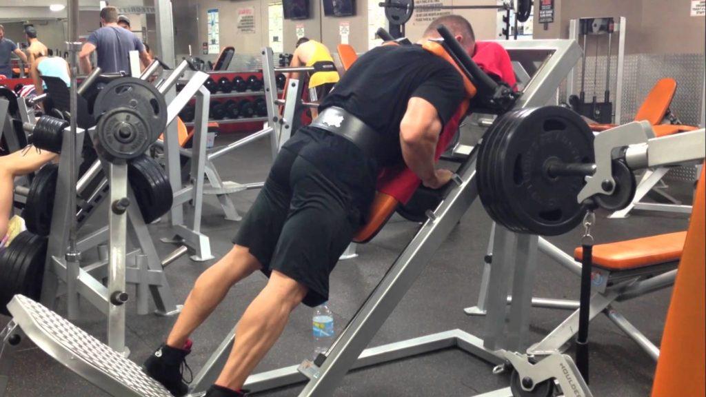 大腿四頭筋を鍛える筋トレの種目であるリバースハックスクワットを行う男性