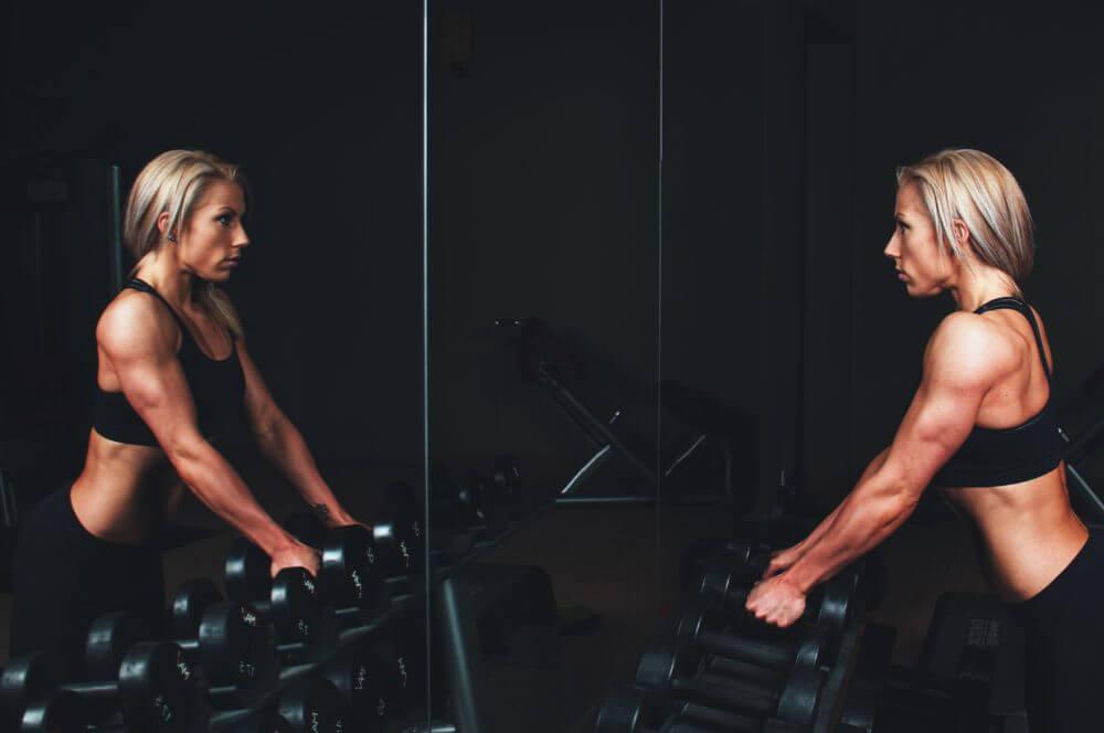 パーソナルトレーニングジムでダンベルを用いた筋トレの指導を受ける女性