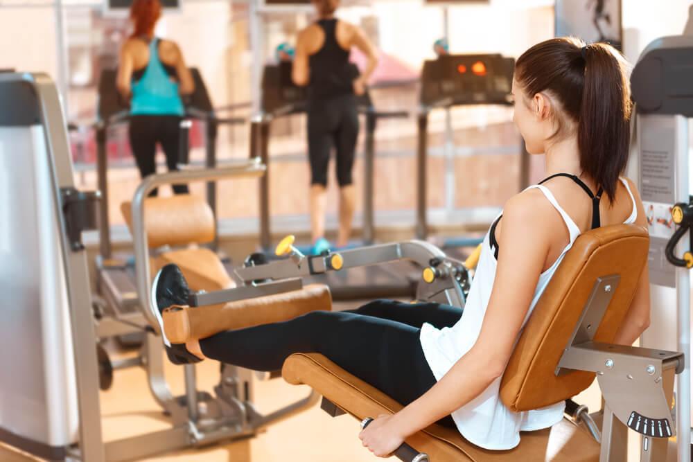 レッグエクステンションで脚を鍛える女性