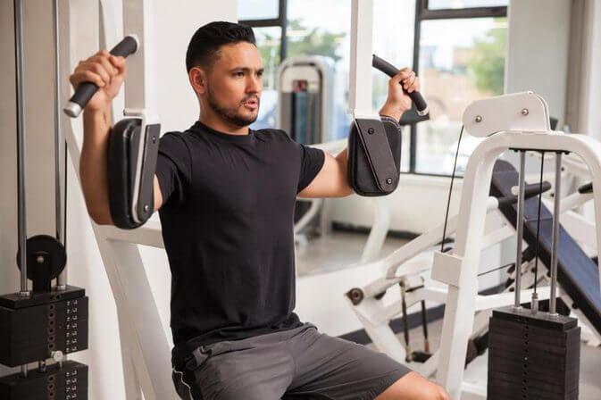 パッド式のペックフライマシンで大胸筋の筋トレをするマッチョな男性