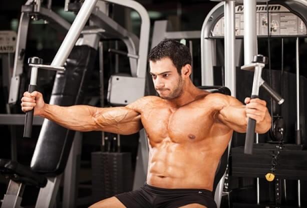 ハンドル式のペックフライマシンで大胸筋の筋トレをするマッチョな男性