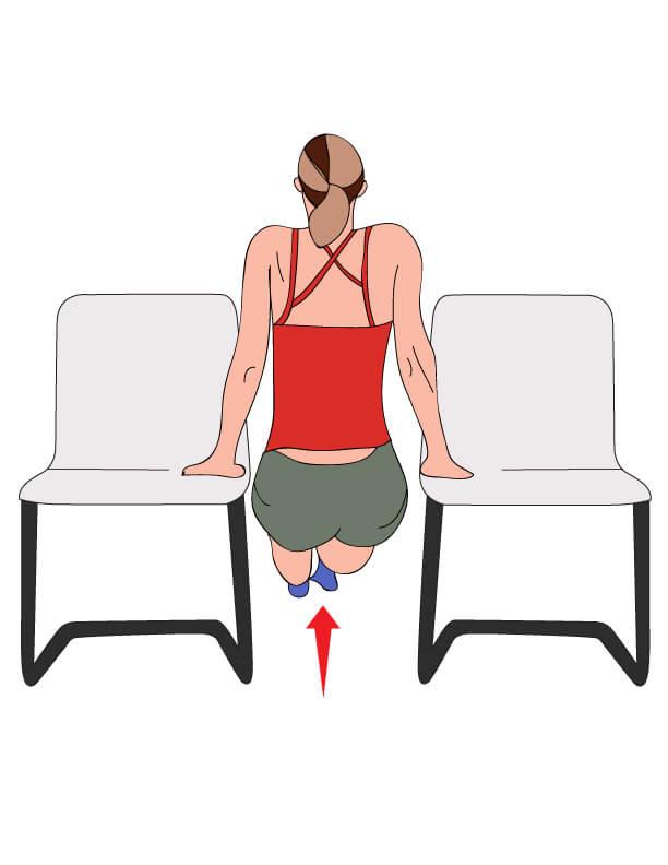 自宅で椅子を使ってディップスをする女性