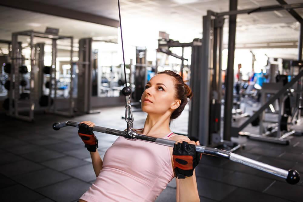 ラットプルダウンで背筋を鍛える女性