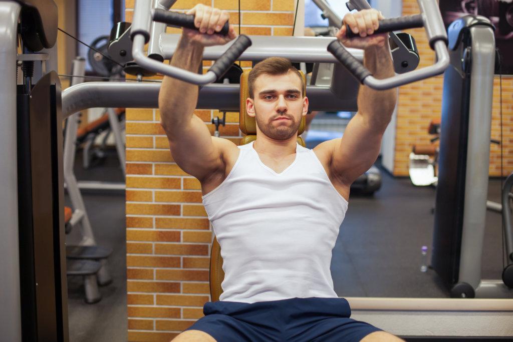 チェストプレスマシンで大胸筋を鍛える男性
