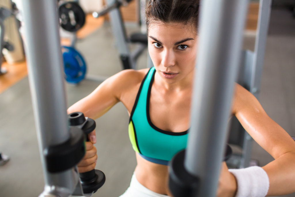 バタフライマシンで大胸筋を鍛える女性